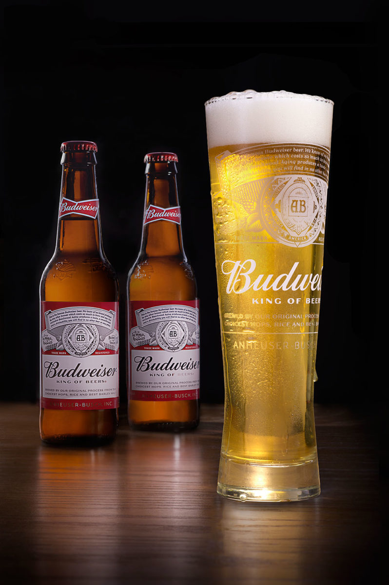 Budweiser with a foamy head in a tall pilsner glass with two bottles standing in the background