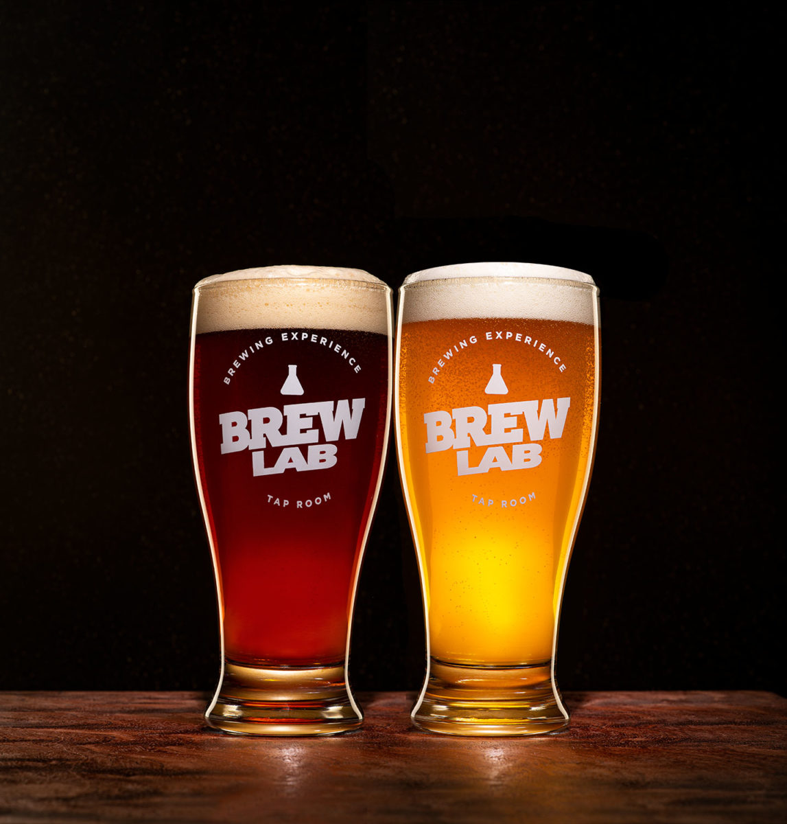 a brown beer and a blond beer in Brew Lab logoed glasses