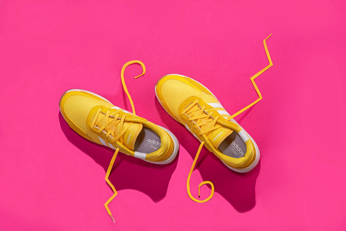 top down photograph of Yellow Adidas tennis shoes on pink background