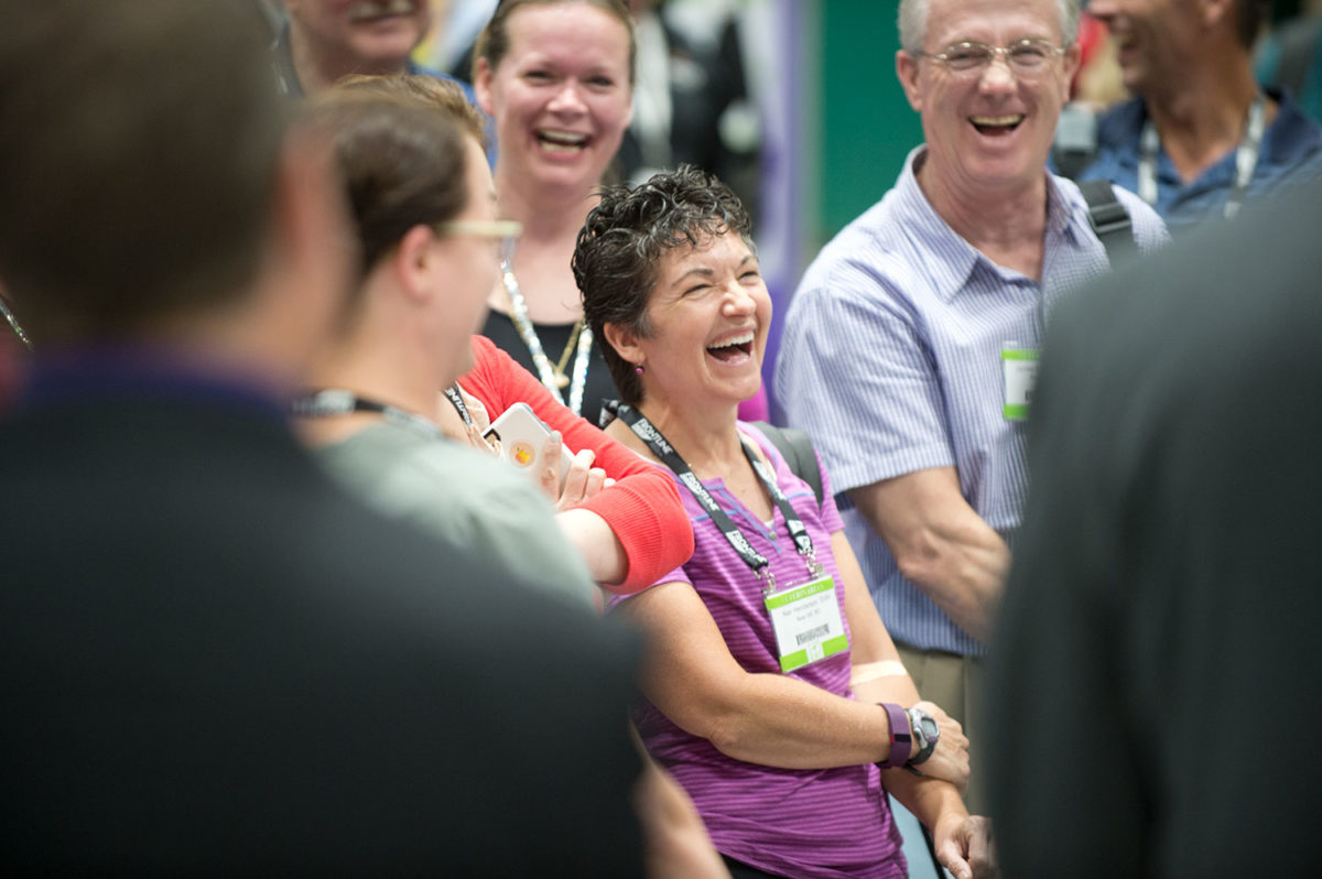 Attendees laughing in a Veterinary Convention exhibit hall