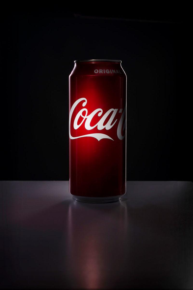 dark mysterious photograph of a coke can spotlight on coke logo