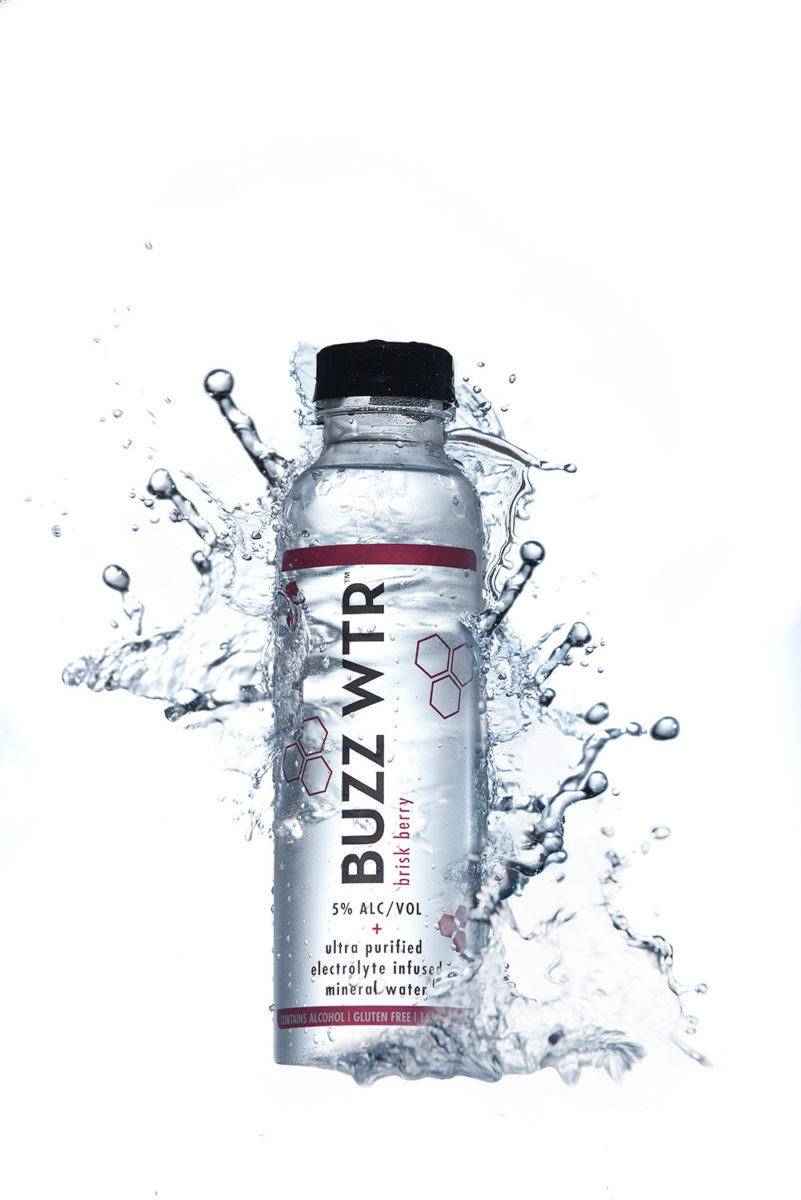 Buzz WTR Brisk Berry bottle with water splashing from behind