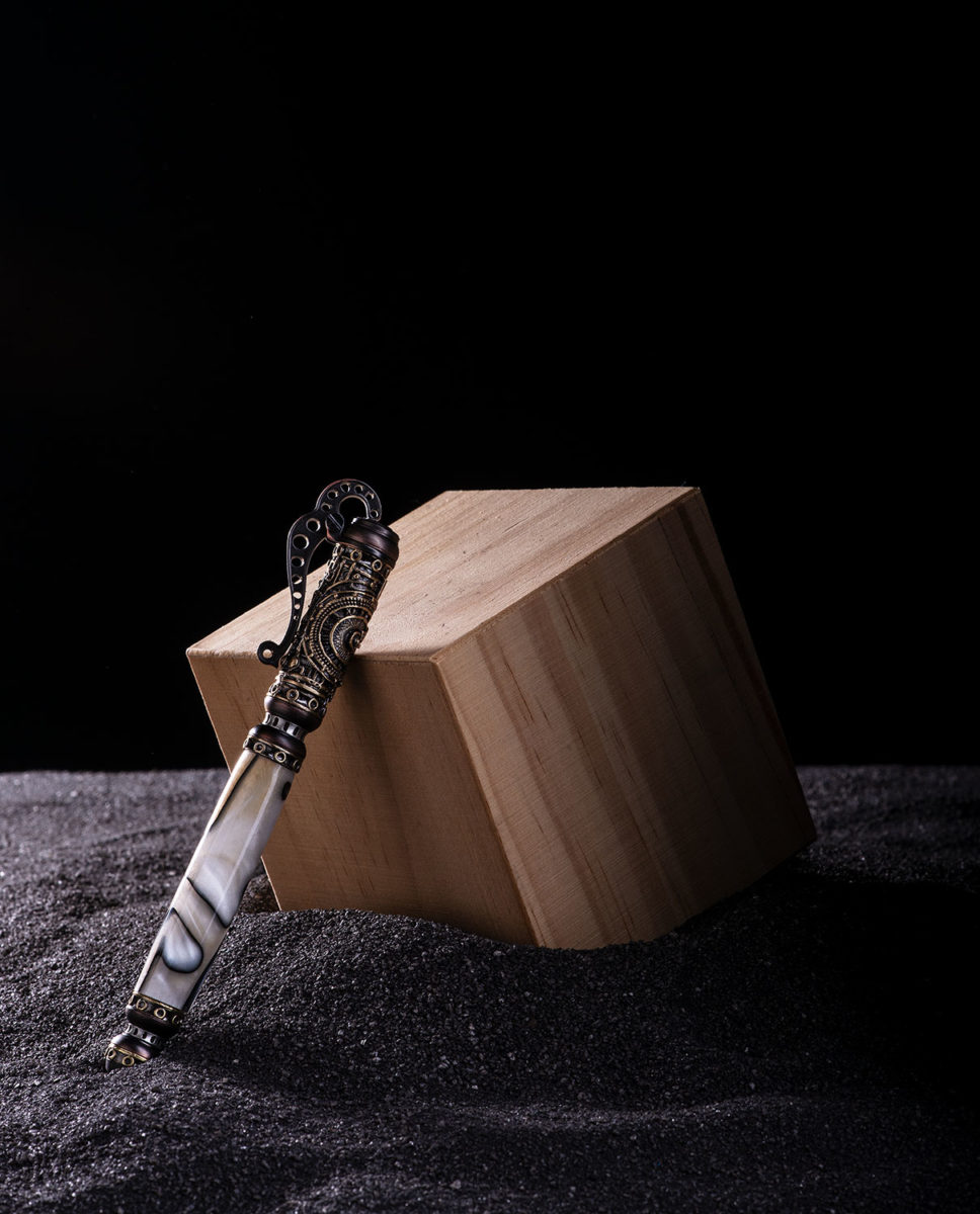 Steampunk Pen leaning against a wooden box surrounded by black sand
