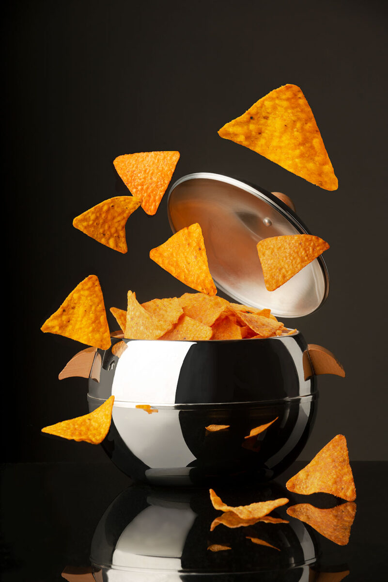 Frozen action photograph of Doritos exploding out of a shiny ice bucket