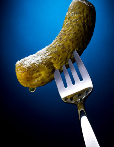 Salted Dill Pickle on a stainless steel fork with a blue background